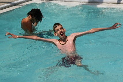 This image shows a photograph of a young man with Marfan in a swimming pool.
