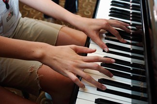 This is a photo of someone with with Marfan syndrome playing the piano, showing their long fingers.